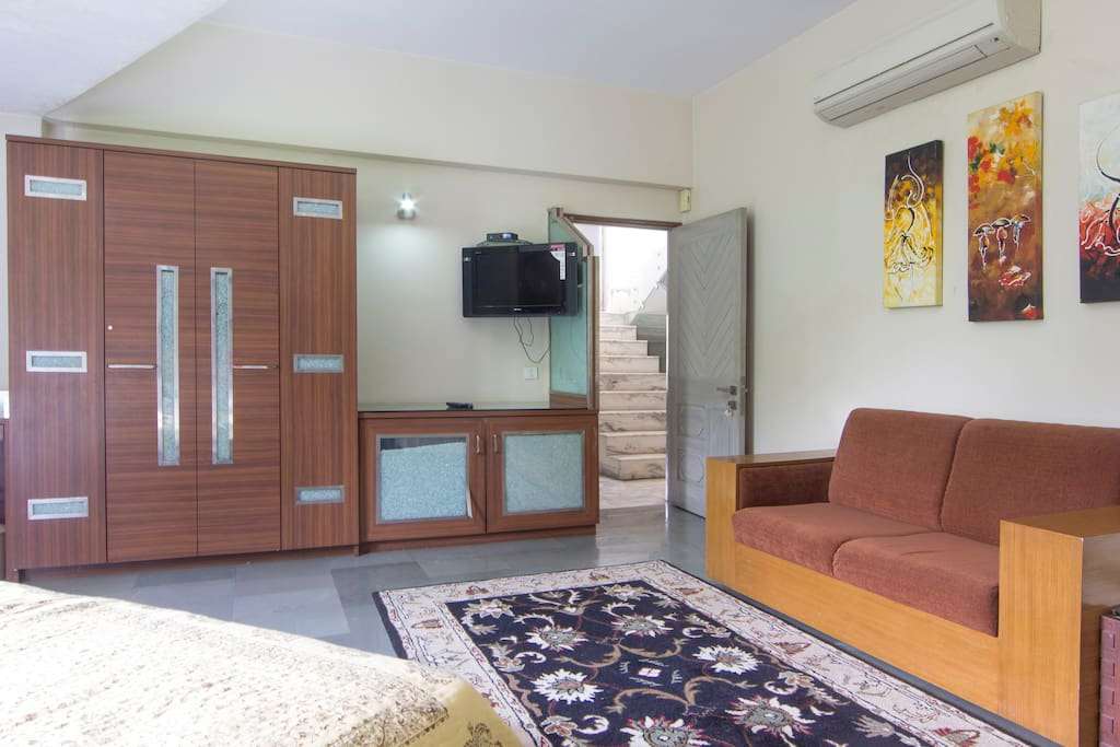 Well appointed bedroom with glass wall for adequate natural lighting, double wardrobe, flat HD TV, mini refrigerator, split AC, work table, etc.