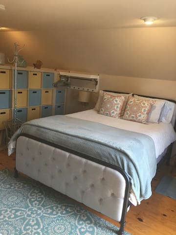 Main sleeping area is separated by a wall of shelving with storage bins. There is a twin bed in the main sleeping area as well. On more twin bed is located at the opposite side of the rental unit.