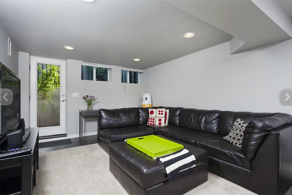 Living area with large couch, TV and DVD player.