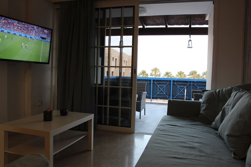 """A confortable sitting room with a sofa/bed a couch and a 42"""" flat TV. The Sofa may be used as is, as an extra single bed, or opened to a spacious and confortable double bed (bedings available at the apartment)"""
