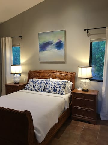 Bedroom is spacious with vaulted ceiling, large walk-in closet, & antique armoire.  Queen sleigh bed and luxury linens. Bedroom doors have locks.  Screened windows & en suite bathroom.  Peaceful & private, surrounded by nature.