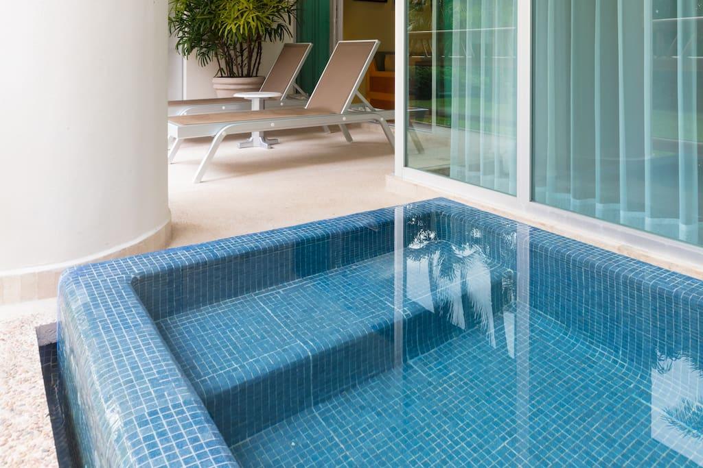Private plunge pool set amid lush tropical foliage.