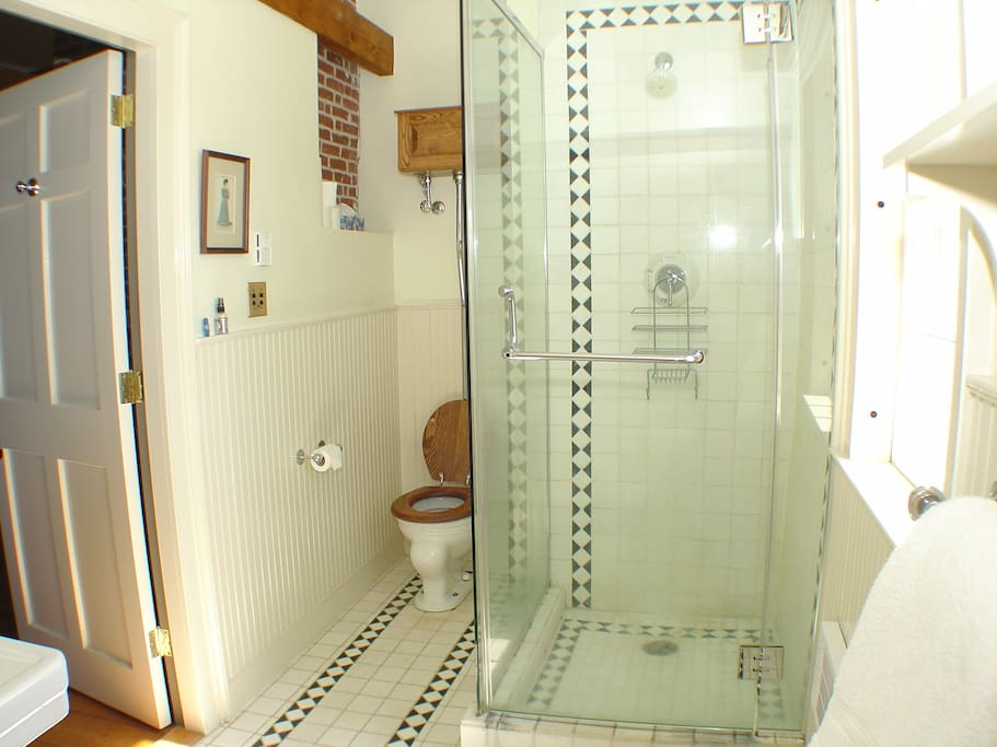 Marble floored glass shower with room to spare.