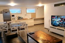 Combined living room and kitchen with table for six people.