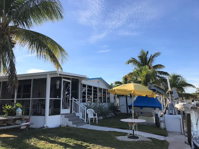 Back yard showing steps and hand rail leading to screened in lanai.  Steps has hand rail.  Motion detector with security lights and wireless security cameras.  26 feet of windows, facing north,  over looking canal that has direct ocean access.