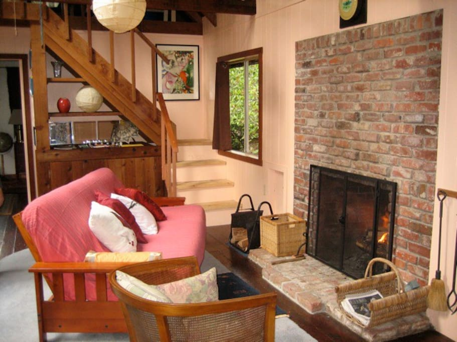 Backing up a little, we see the living room futon couch in front of fireplace, wood provided.