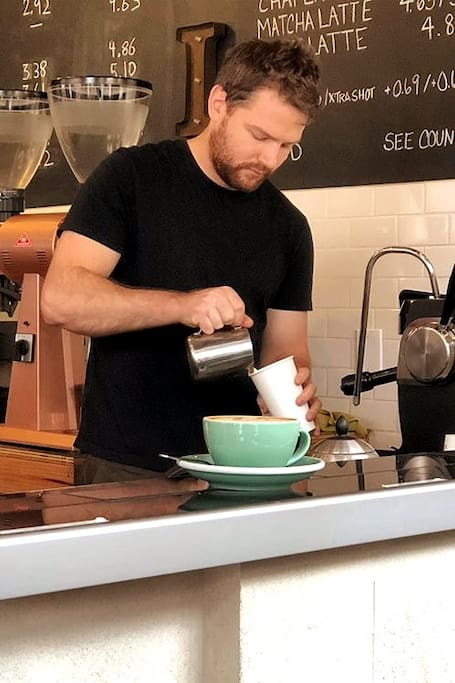 Ross pouring a latte at his shop.