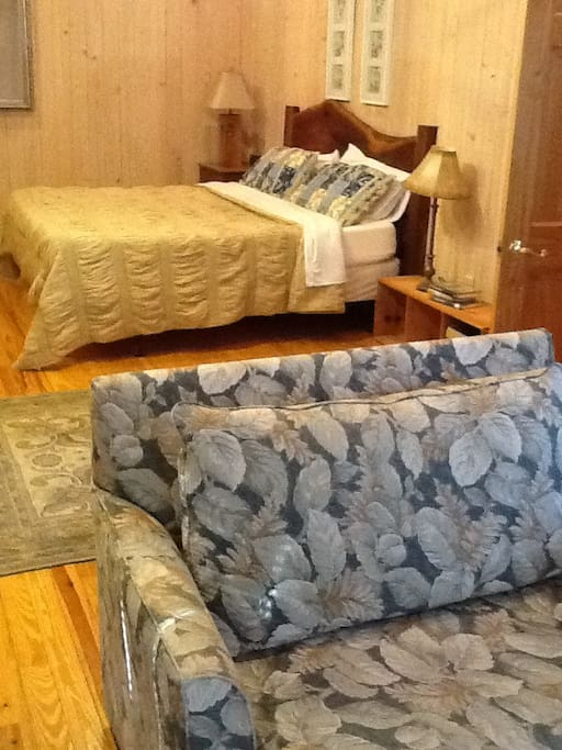 """Extra large master bedroom in the main house has a king sized memory foam mattress and a twin sleeper lounge chair.   This apartment """"treetop lodge"""" sleeps 7"""