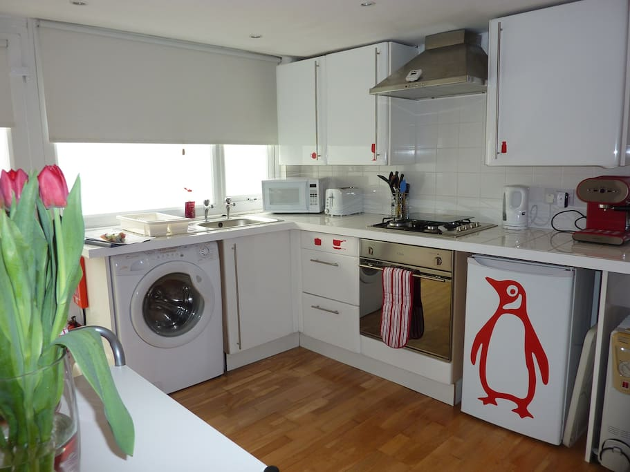 kitchen with washer-dryer, oven, microwave, toaster, coffee machine