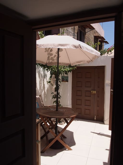first entrance/the courtyard ,sunny with ombrella,a table and 2 chairs to sit and enjoy your breakfast or just coffee or a drink ..there there are the bathroom(shower)and a WC