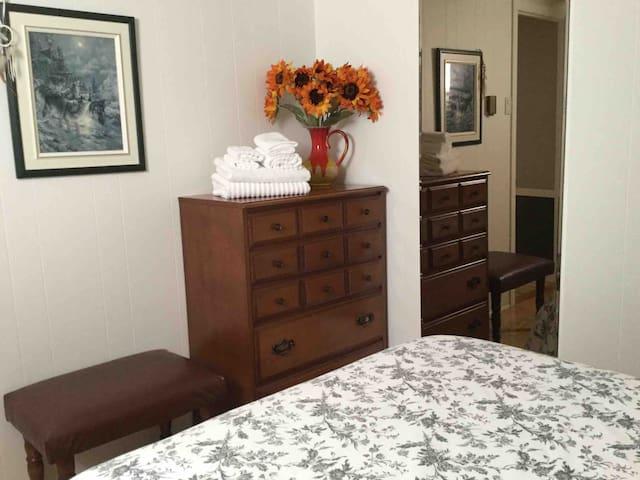 Chambre à coucher comprenant un lit double, une commode et une grande garde-robe.