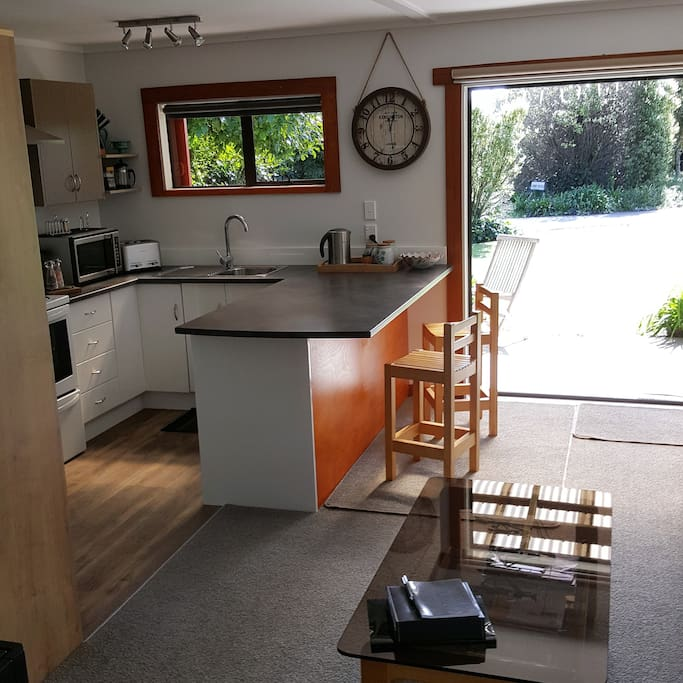 Kitchen with breakfast bar, oven/stove top, fridge/freezer, microwave and full utensils.