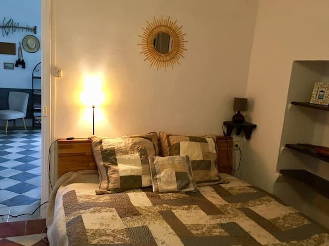 Chambre avec lit 160x200cm, lavabo et grande armoire. Vieille porte-fenêtre qui donne sur le jardin.