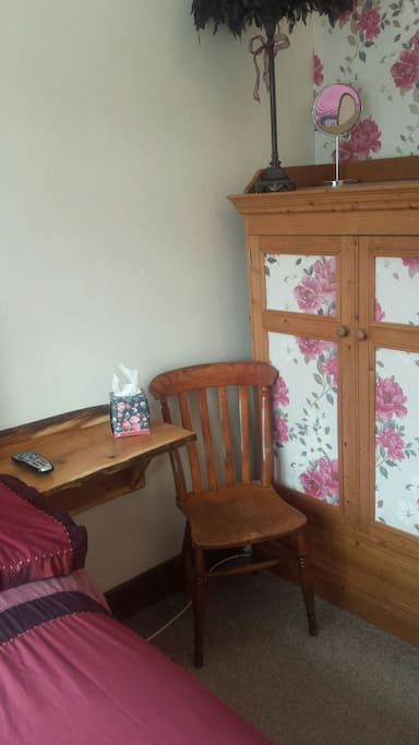 Bedside table and chair. Small wardrobe.