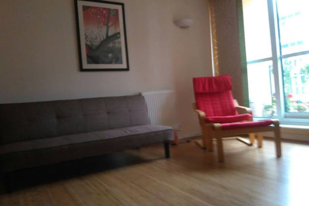 Living room - sofabed, easy chair and footstool, solid bamboo floors, lots of light