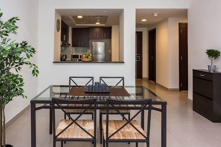 The living room and the kitchen are separated by the dining area that includes a wooden table with sitting spaces for 4 people