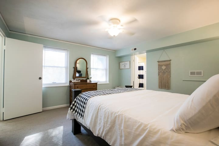 Master suite is filled with natural light and multi-port charging stations on both sides of queen bed