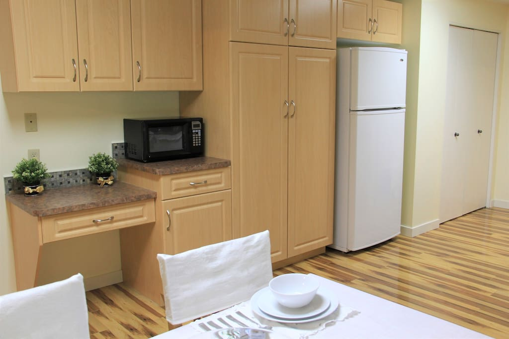 Another view of kitchen showing cabinets and fridge.