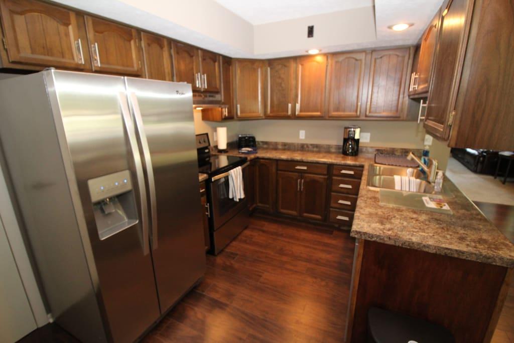 Kitchen, microwave, refrigerator, coffee maker, toaster, oven/range.