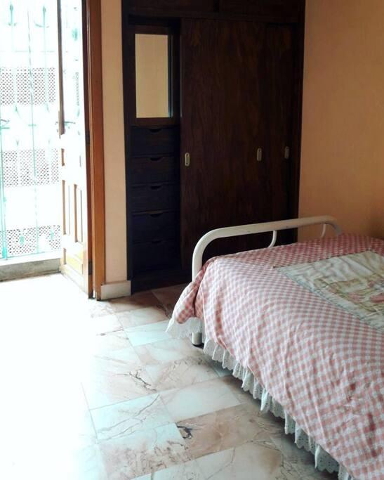 Recámara para una persona con balcón, clóset, ventilador de tocador y ropa de cama incluidos.