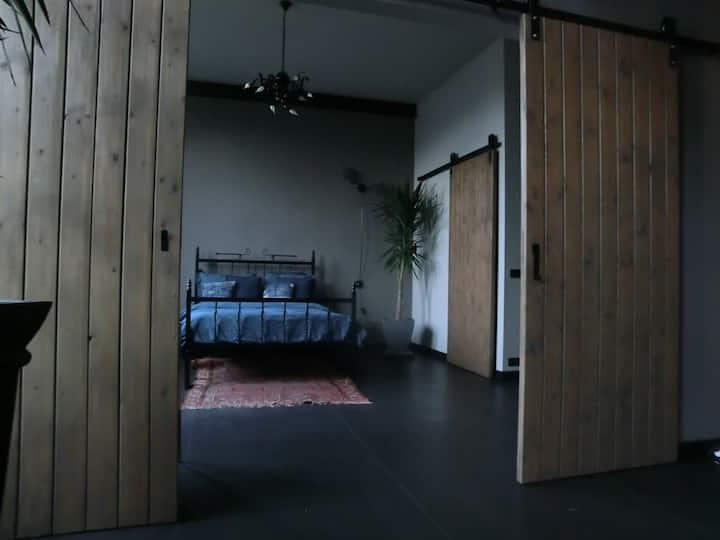 Slaap- en badkamer in loft in voormalige fabriek.