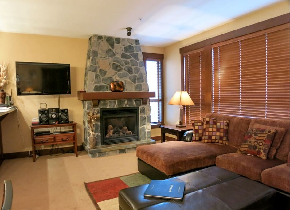 Spacious, light living area with large fireplace