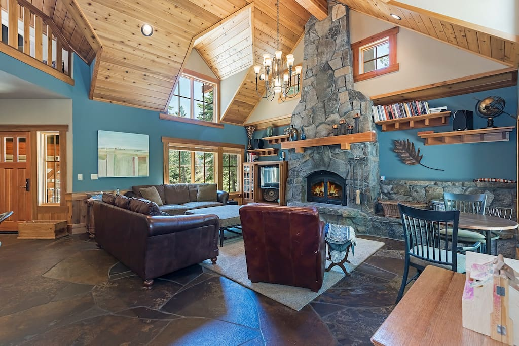 Soaring ceiling in great room with large granite fireplace, cozy furnishings.