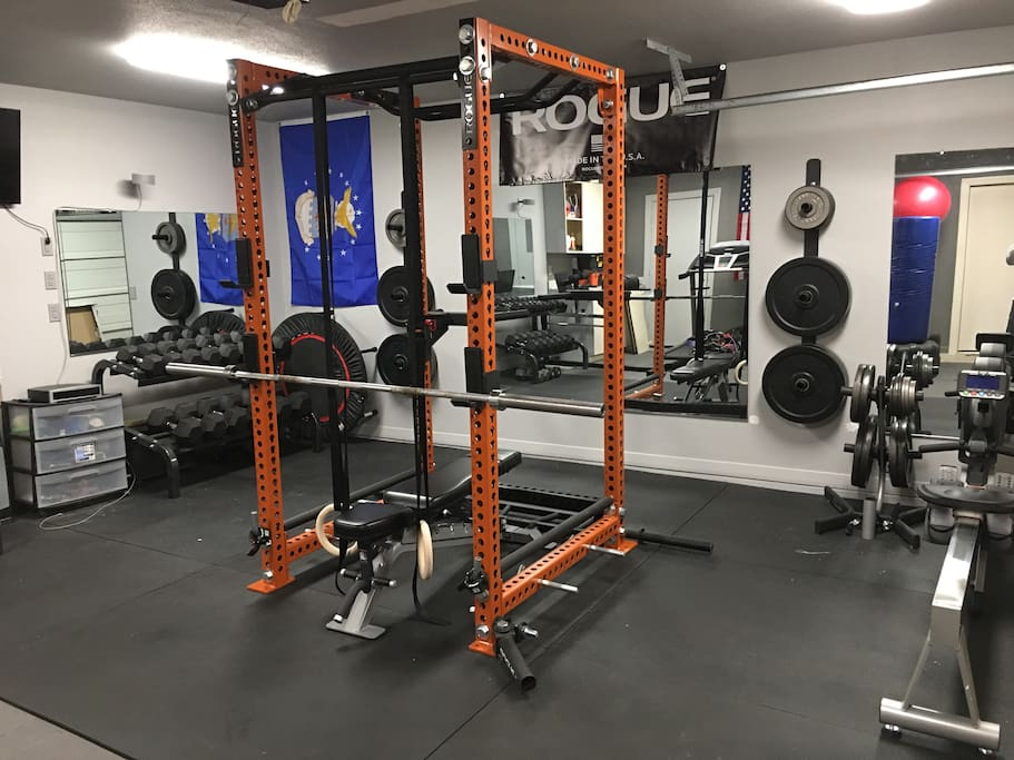 Garage gym with free weights, dumbbells, treadmill and rowing machine.