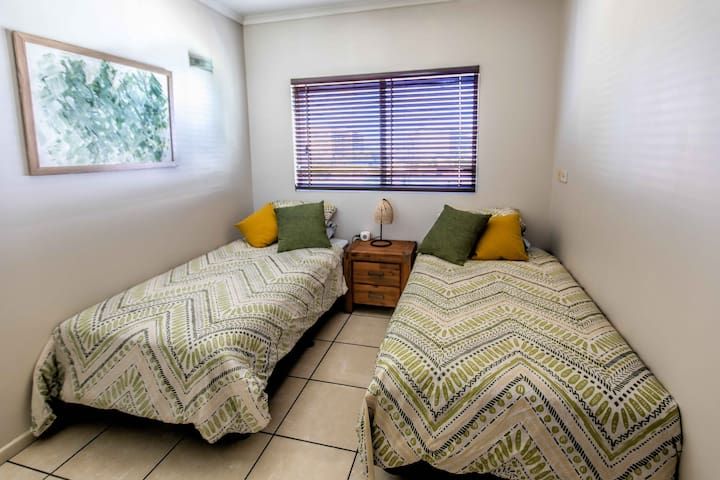 Bedroom 1 contains 2 king single beds with quality linen and air conditioning