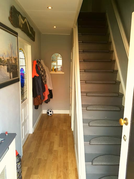 Entrance with stairs, coat rack and first toilet.