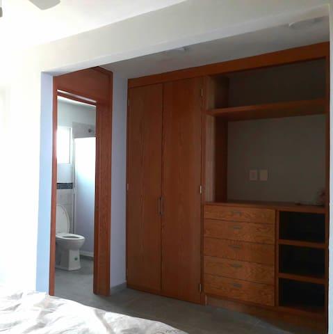 Closet de madera en el cuarto principal con cajones y espacios para colgar ropa.