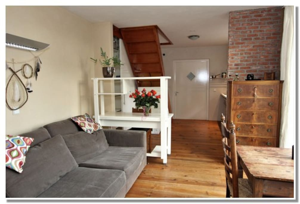 Woonkamer, rechtsvoor openslaande deuren naar buiten. Achteraan rechts de keuken. Linksachter trap naar boven (slaapkamers). Helemaal achteraan eigen entree