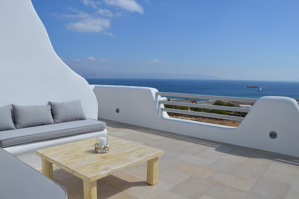 20m2 veranda in the 1st floor with a cozy sitting area, a panoramic sea view and a separate access to the garden via outdoor stairs