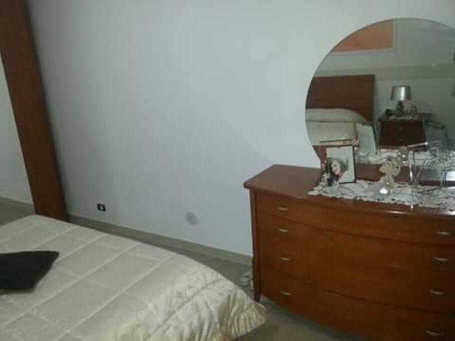 Mobile vicino al letto con specchio