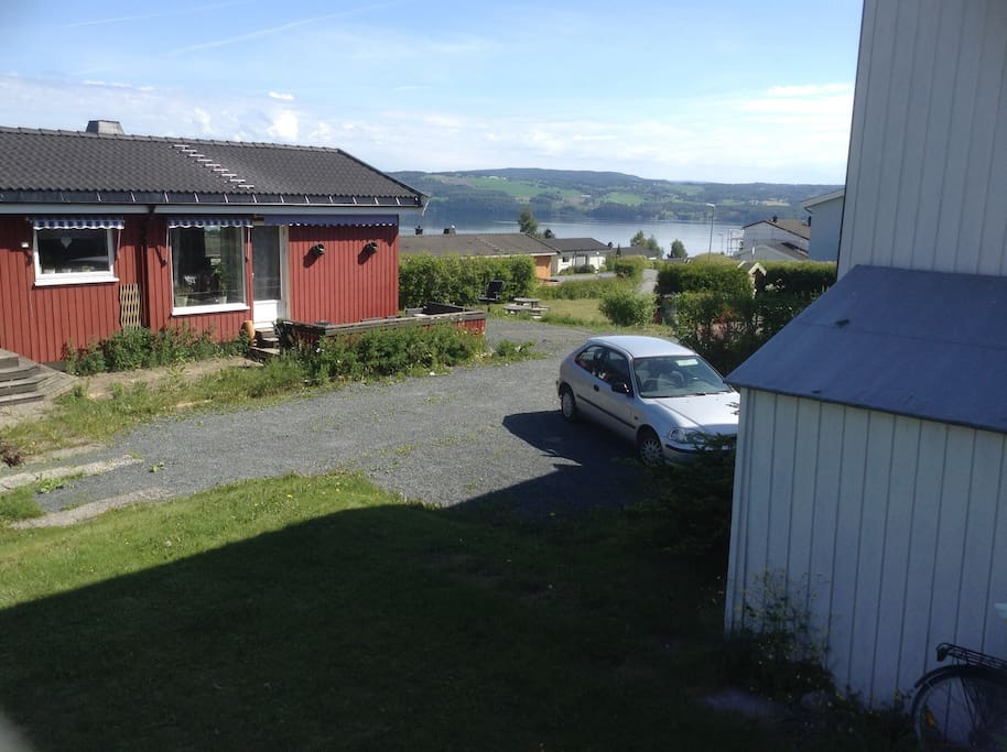 Utsikt fra huset m parkeringsplassen.