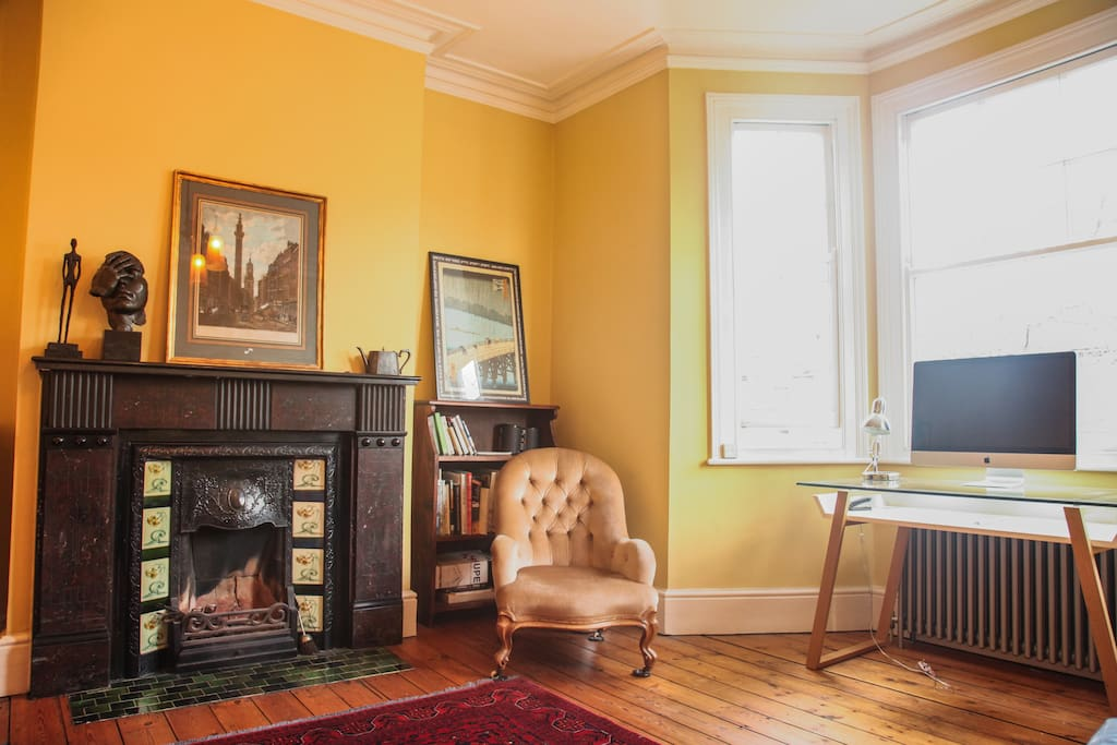 Lounge/living room with original Victorian fireplace. There is also a single bed which can be used as a sofa, as well as three armchairs and a desk.