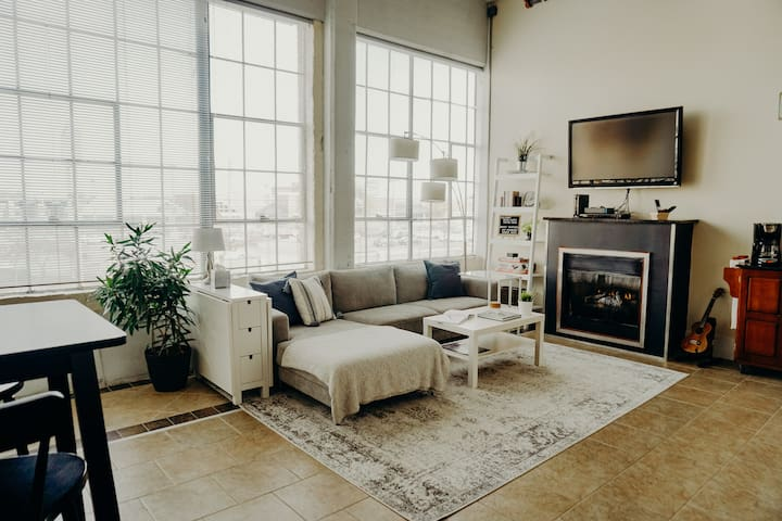 An open living room with huge factory windows lets in incredible natural light. A remote controlled gas fireplace helps keep the place cozy during colder weather.