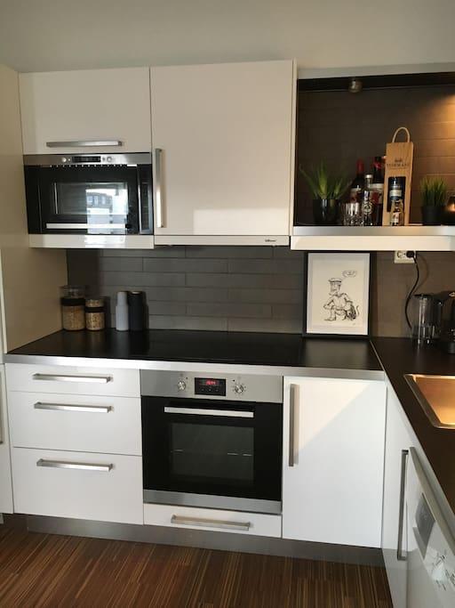 Kjøkken med hvitevarer, komfyr, mikrobølgeovn og nespressomaskin.