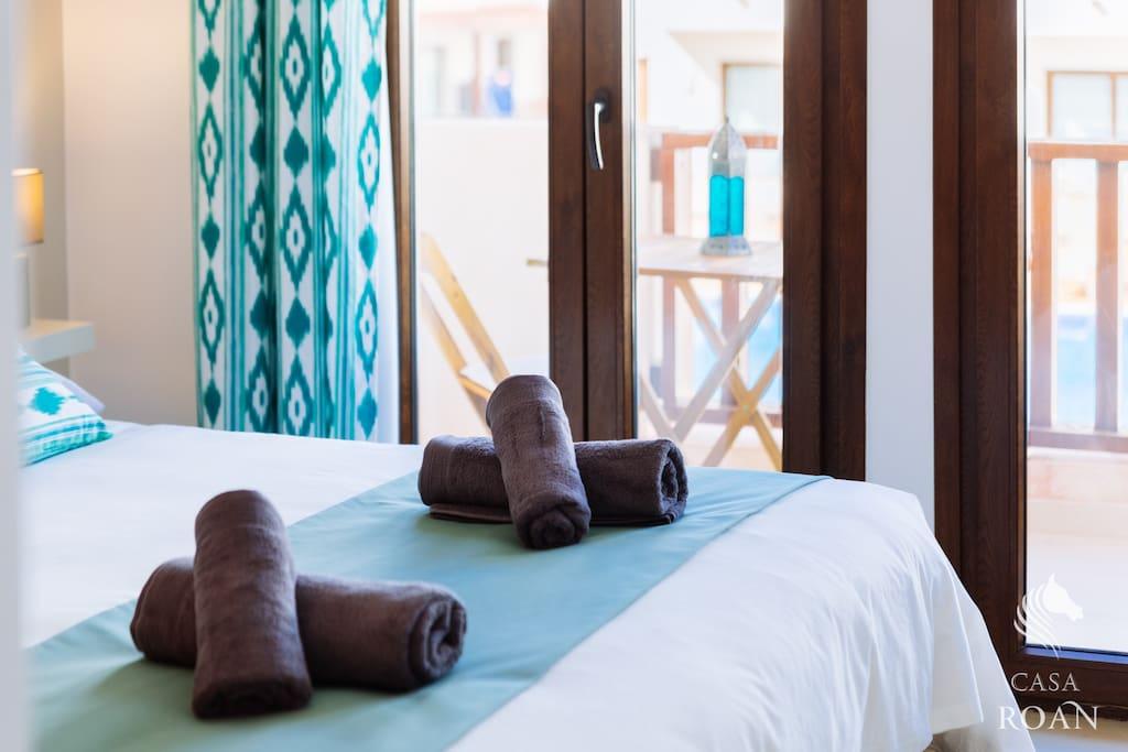 Dormitorio con terraza y vistas a piscina.
