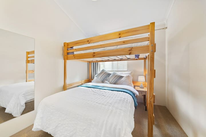 2nd bedroom with plush double bed, king single loft bunk bed, floor length mirror, tower fan and large built in wardrobe.