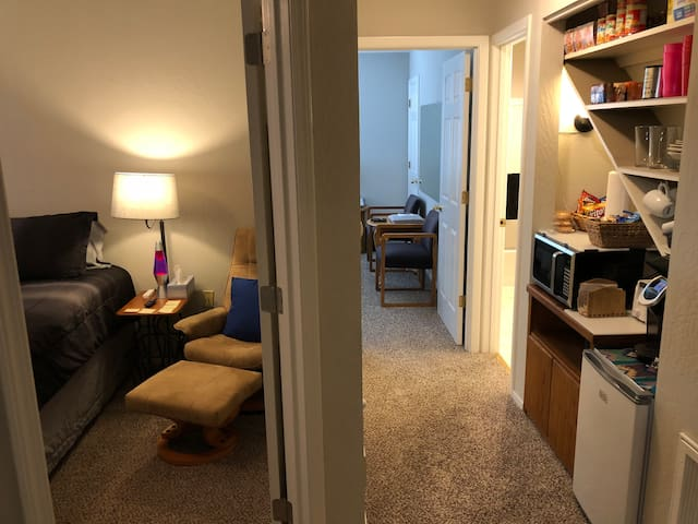 Looking down the hallway of the suite from the gym. You see bedroom #1 on the left, the kitchenette on the right, then the bathroom on the right past the kitchenette, and then the 2nd bedroom (which can be set up as a private living room) at the end.