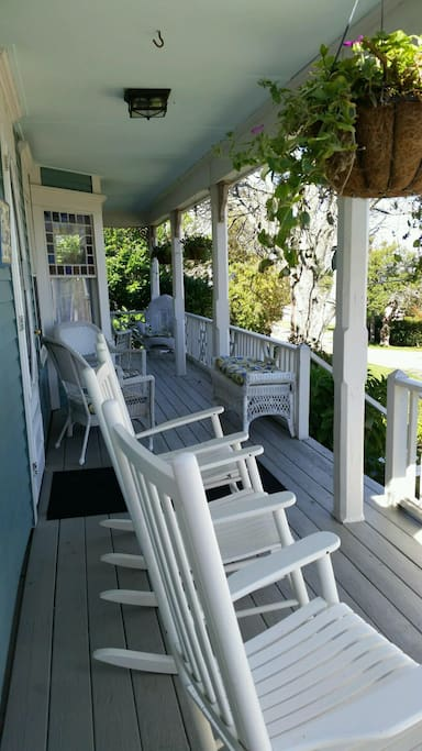 Expansive wrap around front porch with rockers and wicker furnishings