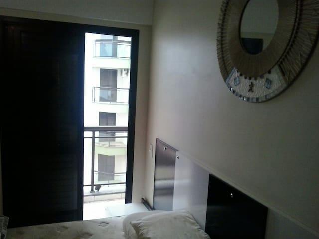 Segundo quarto com cama queen, ventilador de teto, armários embutidos e varanda.