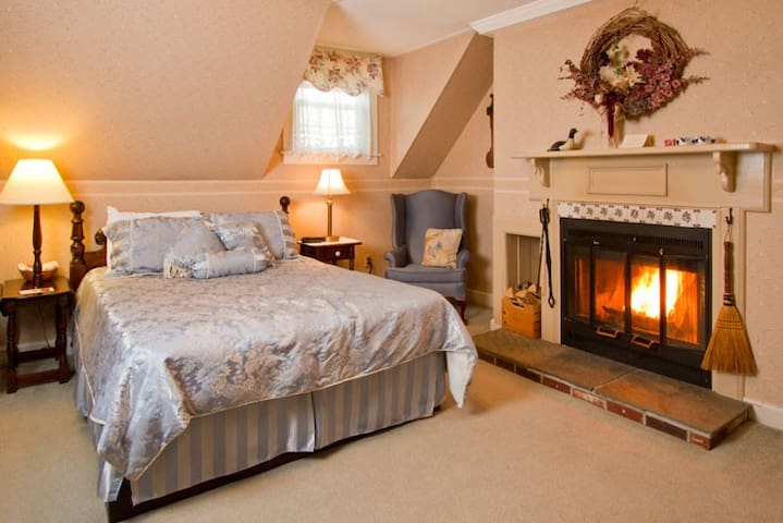 Bedroom 1 with queen bed and wood burning fireplace.