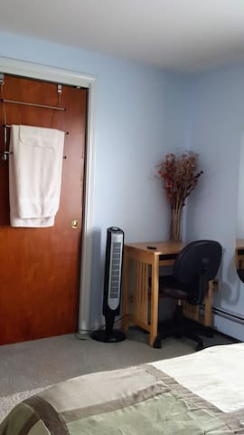 A desk, tower fan, closet & towels