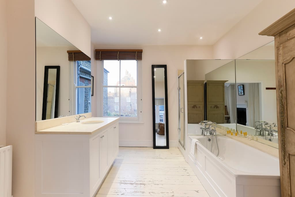 The master bedroom's ensuite bathroom, bright and modern, has a separate bath and shower.