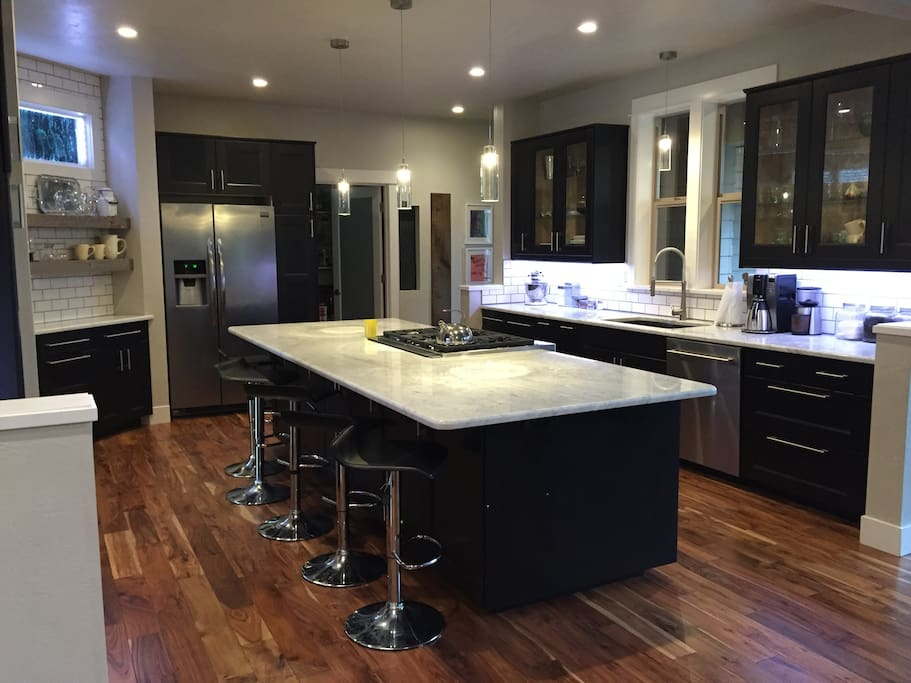 Kitchen features Carrera Marble countertops, white subway tile and gourmet appliances