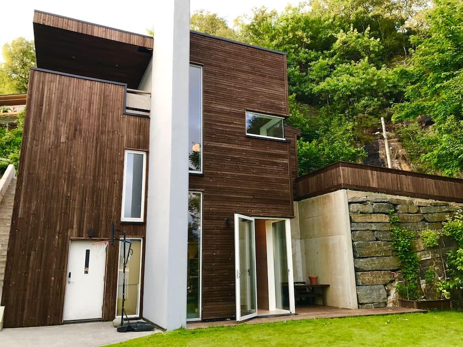 Nybygget funkishus med leilighet over tre plan. Skjermet uteplass til høyre for huset.