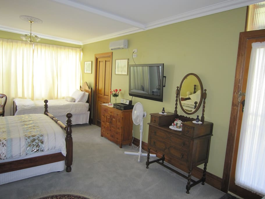 General view of room showing door to en suite to the left with furniture and TV. To the extreme right is the door providing your private entry.
