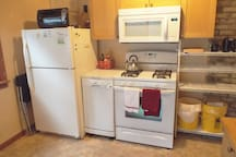 The kitchen is equipped with a gas stove, microwave, refrigerator, small dishwasher, coffee maker, toaster, toaster oven, rice cooker, mixer, cookware, dishes, and cutlery.
